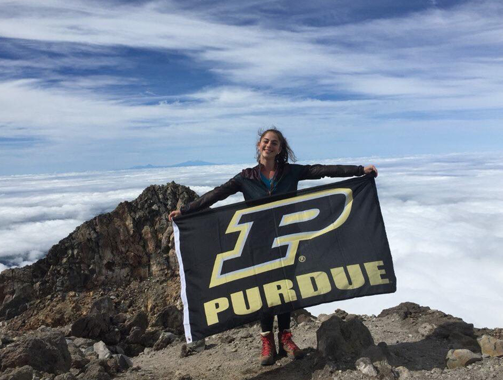 student holding purdue flag on mountain top